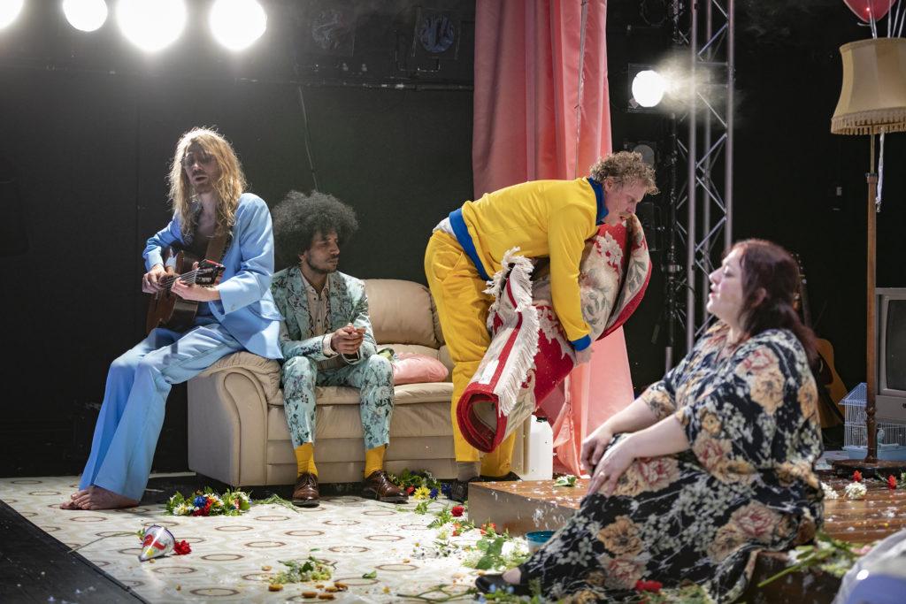 Regionteatern. Balladen om Nygatan 8. Skådespelarna på scen sjunger, städar, sitter och spelar musik.