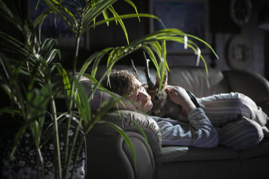 Regionteatern. Balladen om Nygatan 8. Björn Johansson Boklund ligger i en soffa och håller om ett uppstoppat huvud.