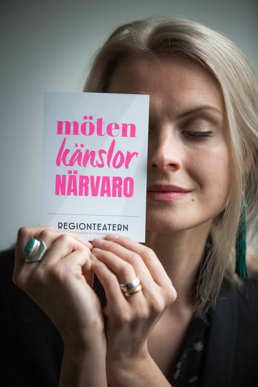Regionteatern. VD-Therese Willstedt håller i ett vykort med Regionteatern grafiska-design.