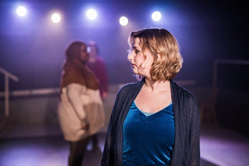 En bild på de tre medverkande i föreställningen. I förgrunden syns Ellie tydligt, hon tittar åt vänster. I bakgrunden syns Iman och Maria suddigt.