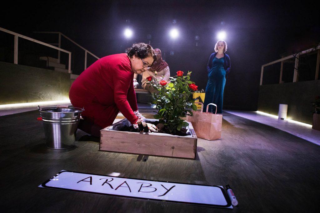 I förgrunden sitter Maria och planterar en rosbuske. I bakgrunden står Iman och Ellie och tittar på.