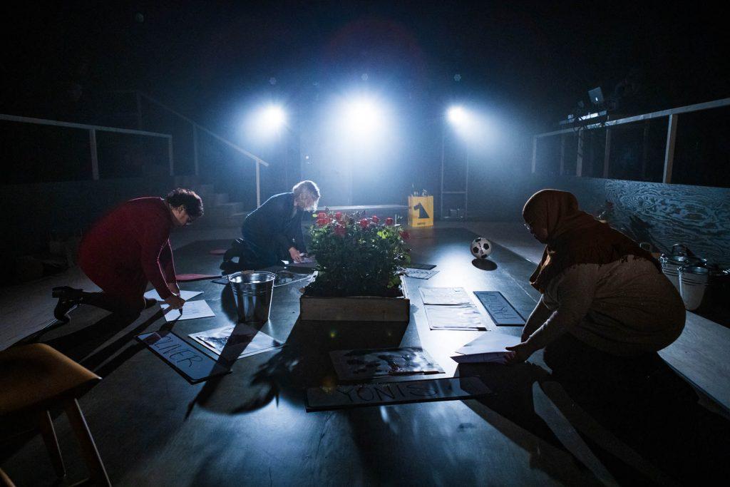 Maria, Ellie och Iman sitter på knä i scenografin och skriver på skyltar. I scenografin syns också en planterad rosbuske, en gul kasse och en fotboll.