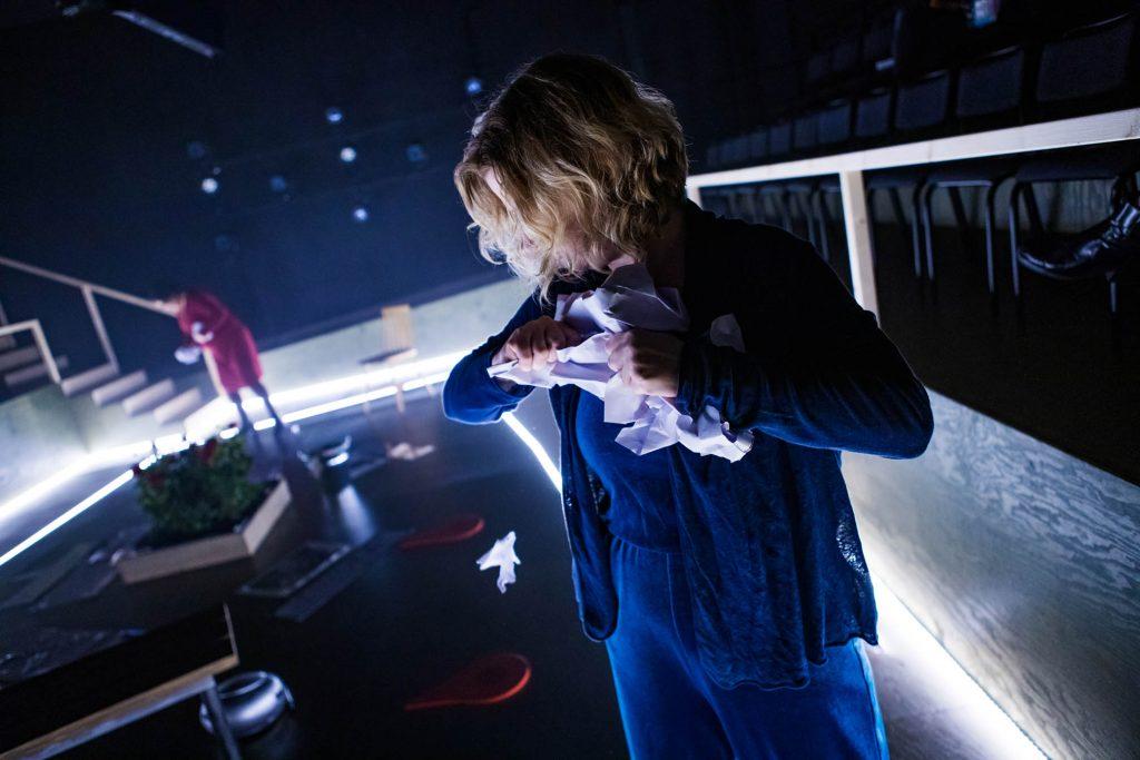 Bilden föreställer Ellie som står längst fram och river ett papper. I bakgrunden syns Maria.